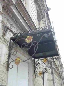 Стеклянные цветы, выполненные в технике витража Тиффани украшают кованый козырек